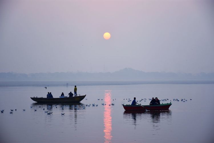 People on boats sailing in river against sky during sunrise