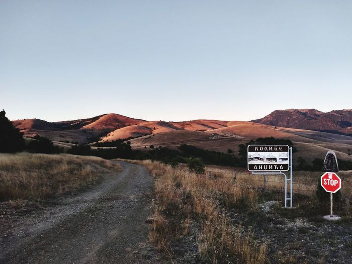 Road sign by mountain against clear sky