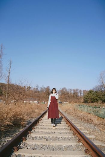 Full length of woman standing on railroad tracks against clear sky