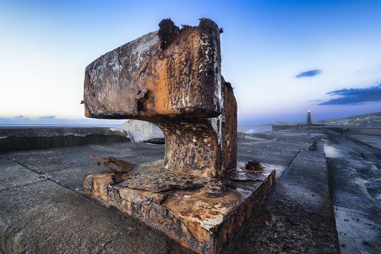 Wood on rock by sea against sky