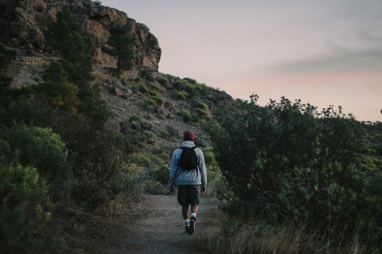 FULL LENGTH REAR VIEW OF MAN WALKING ON MOUNTAIN
