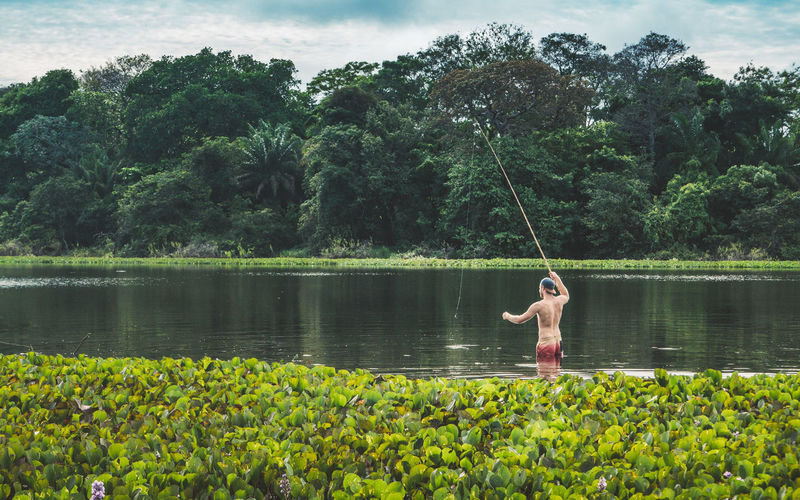Rear view of shirtless man fishing in lake
