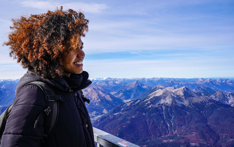 Side view of smiling young woman standing on mountain