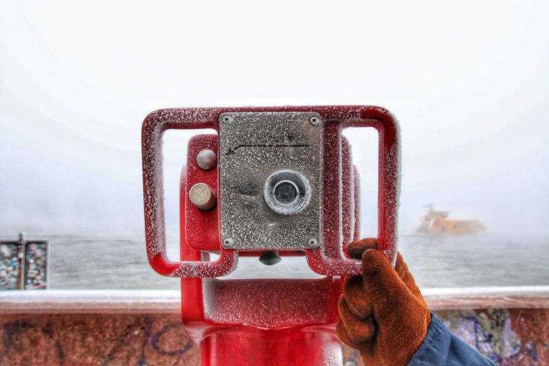 Cropped Image Of Person Holding Coin-Operated Binoculars At Harbor During Winter