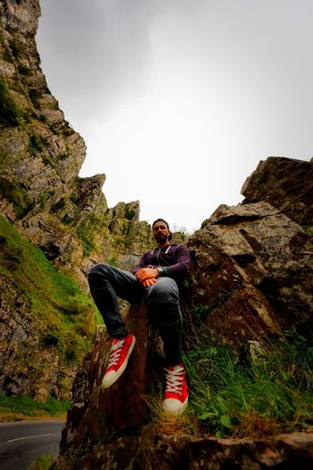 Low angle view of man sitting on rock formation against sky at cheddar gorge
