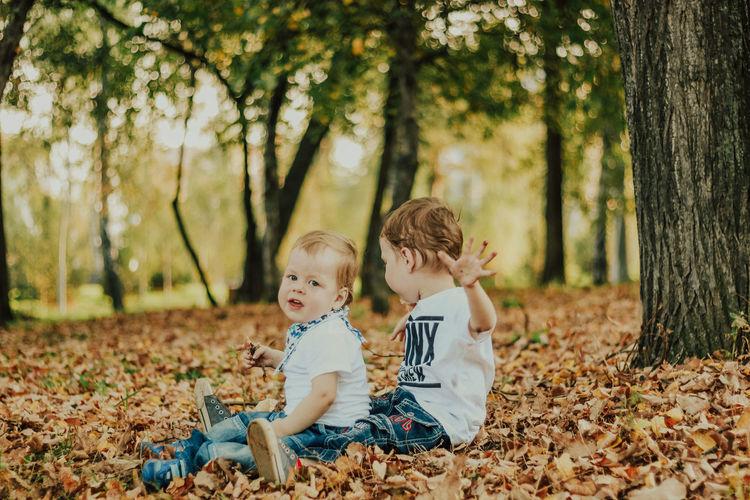 Siblings sitting on land against trees