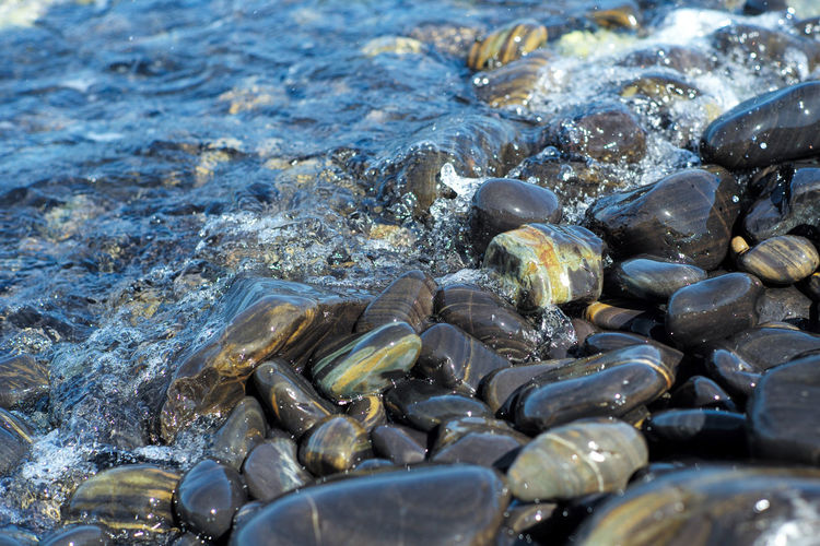 Closeup group of wet polished stones and pebbles were surfed by the sea