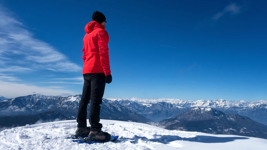 Man Standing On Snowcapped Mountain Against Blue Sky