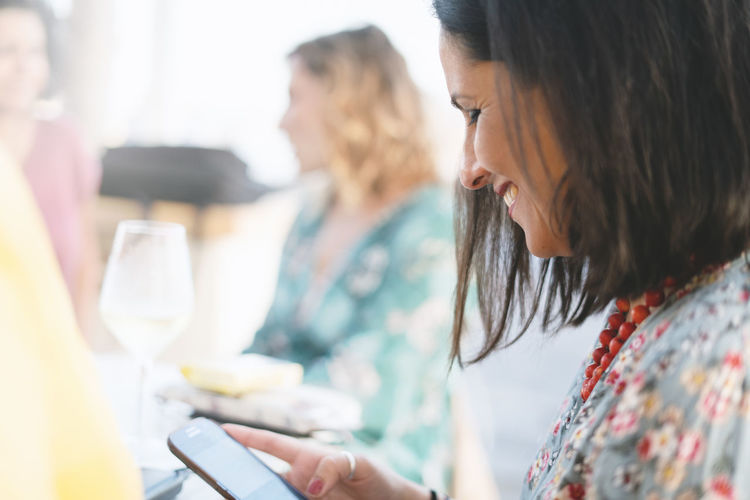 Close-Up Of Woman Using Phone While Sitting In Restaurant