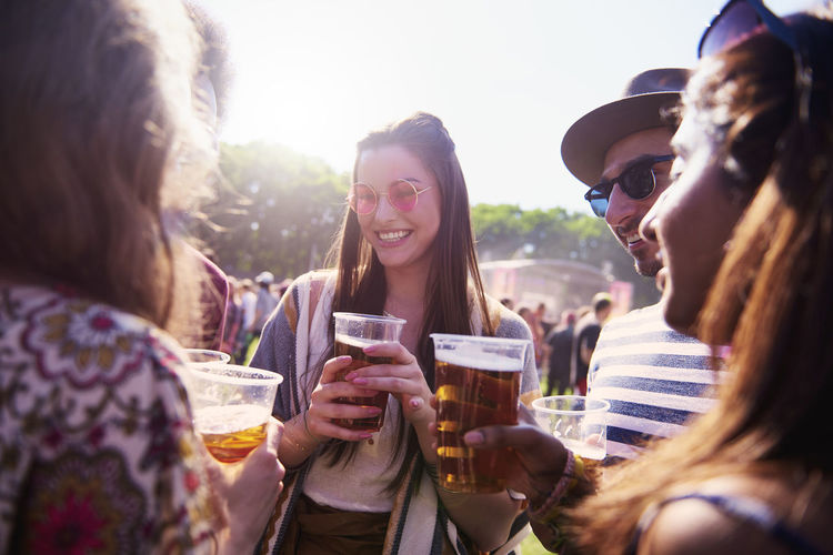 Friends enjoying beer in party during sunny day
