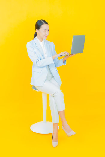 Full length of woman standing against yellow background