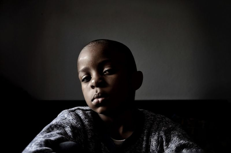 Portrait Of Boy Sitting At Home Against Wall