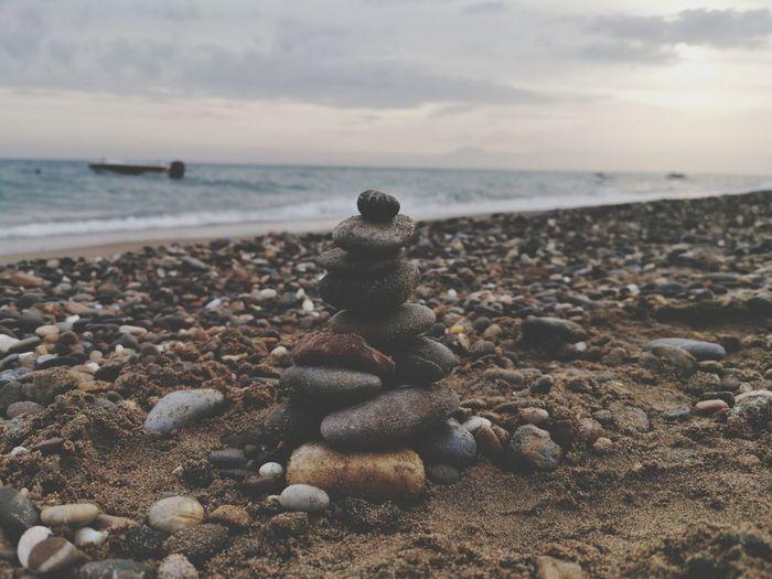 Pebbles on beach against sky