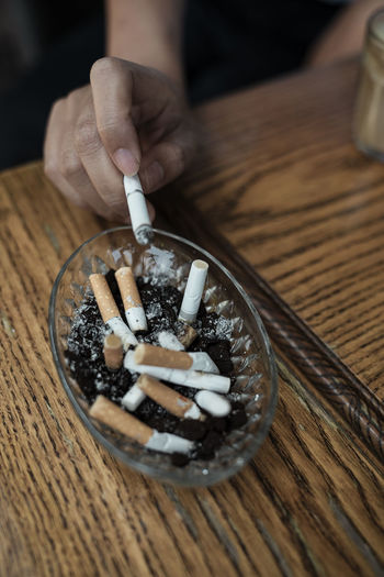 Close-up of hand holding cigarette on table