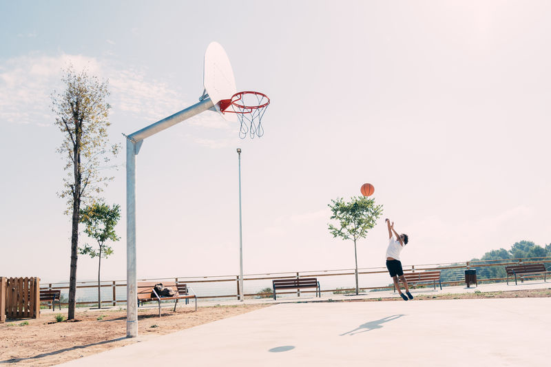 Full length of boy playing basketball in court against sky