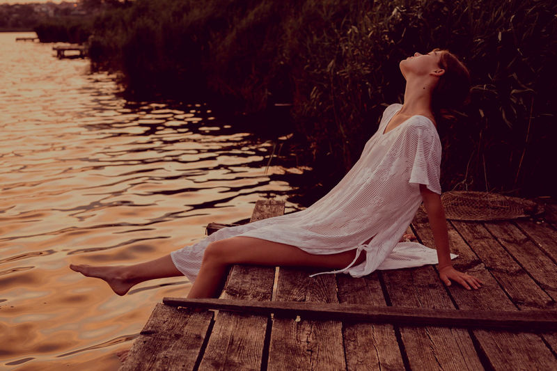 Low section of woman relaxing on wood