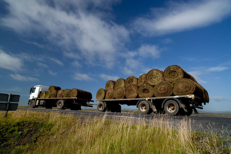 Grass Bales Transported In Semi-Truck Against Sky