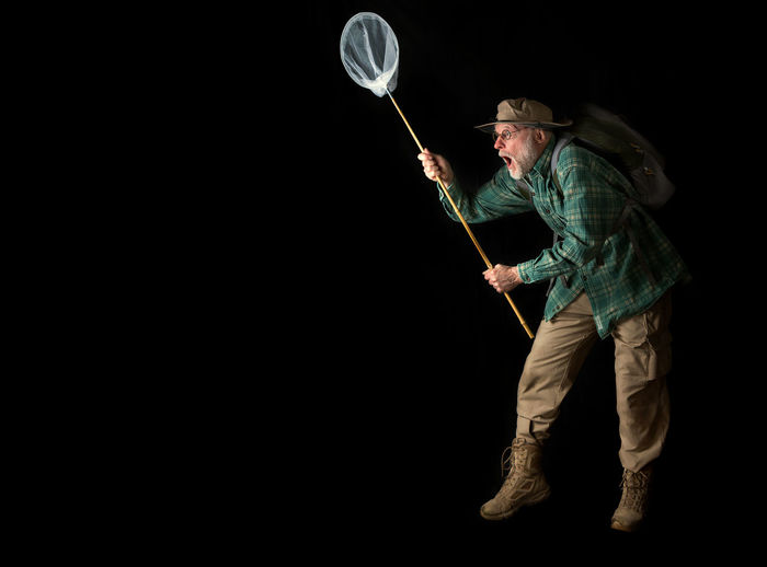 Full length of man holding butterfly net against black background