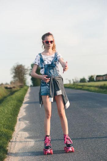 Full length of girl roller skating on road
