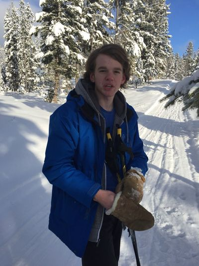 Portrait Of Young Man Wearing Mittens While Standing On Snowy Field