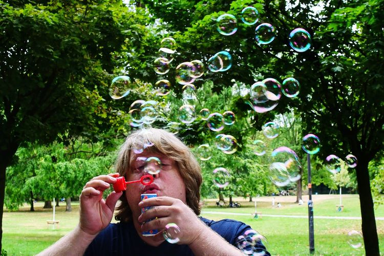 Man blowing bubbles against trees in park