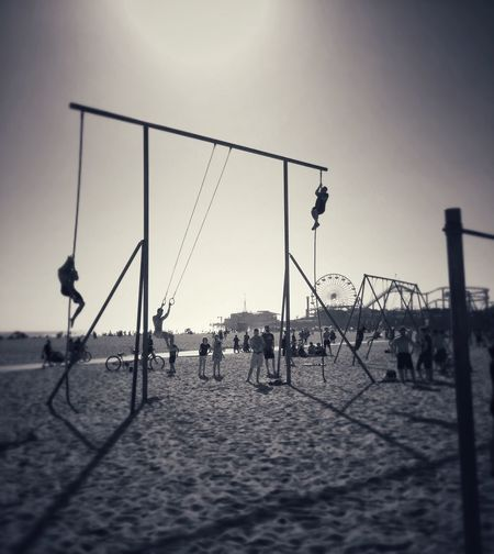 People on swing at beach against clear sky