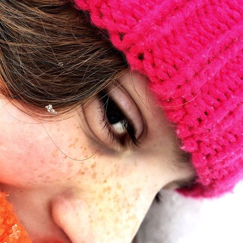 Close-Up Portrait Of Girl Wearing Pink Knit Hat During Winter