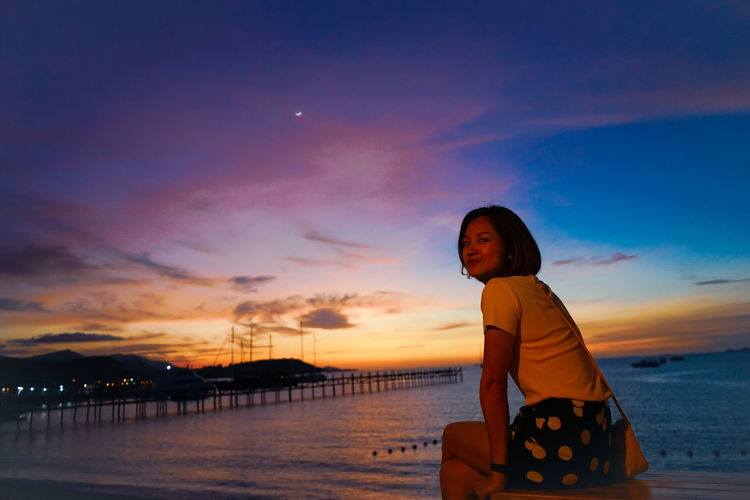 Portrait of woman sitting by sea against sky during sunset