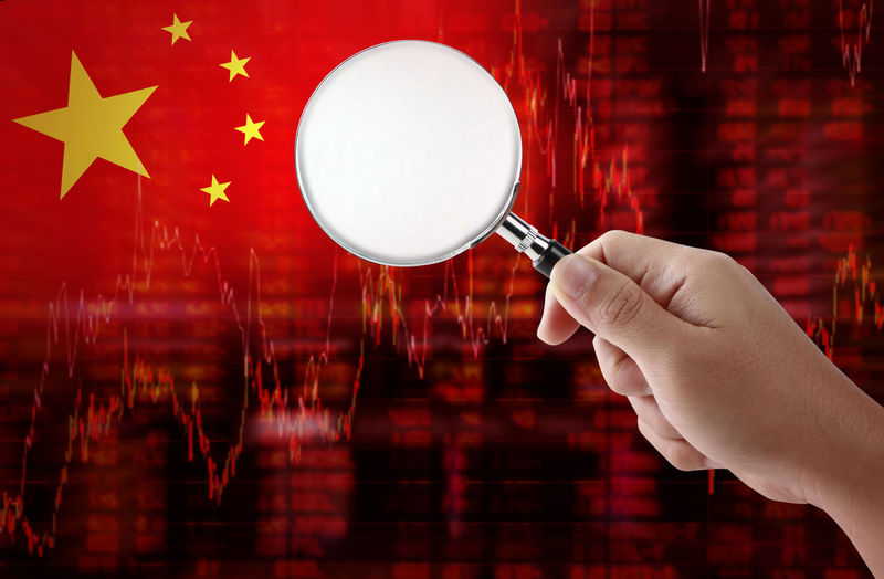 Digital composite image of cropped hand holding magnifying glass against chinese flag