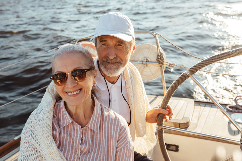 Smiling senior couple standing at boat