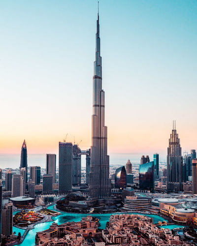 Burj khalifa in city against sky during sunset