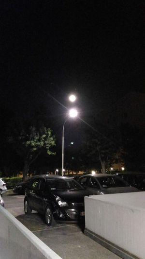 Cars on illuminated city against sky at night