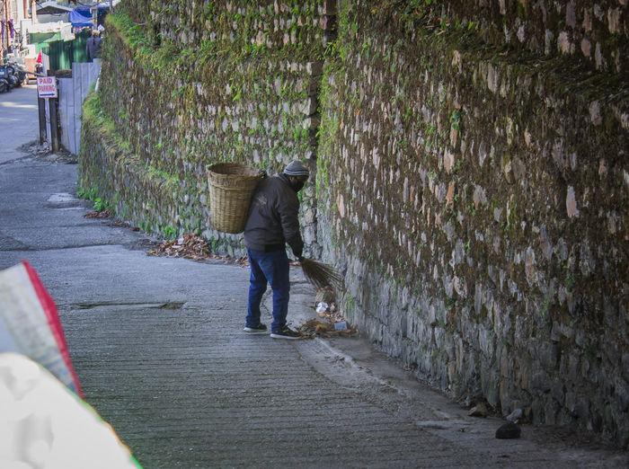 Rear view of woman walking on footpath by street