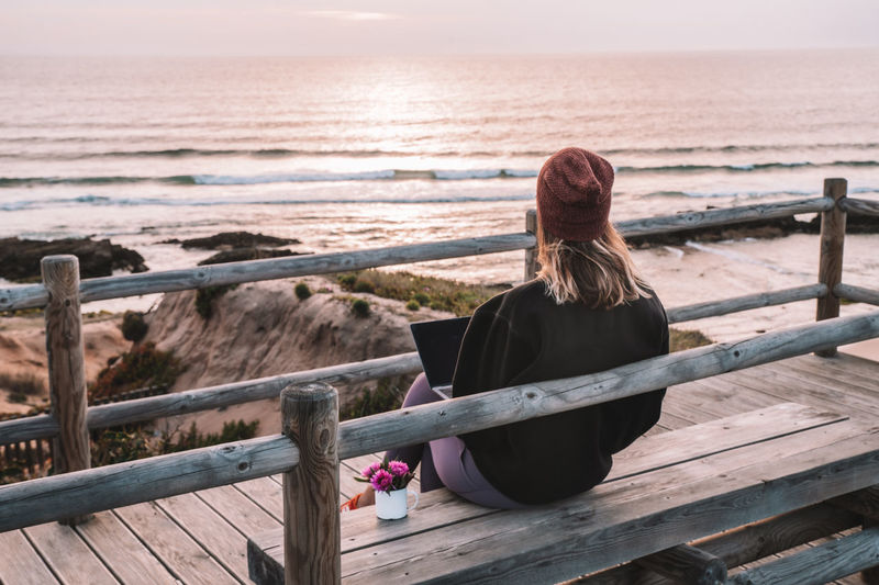Rear view of woman sitting on railing against sea