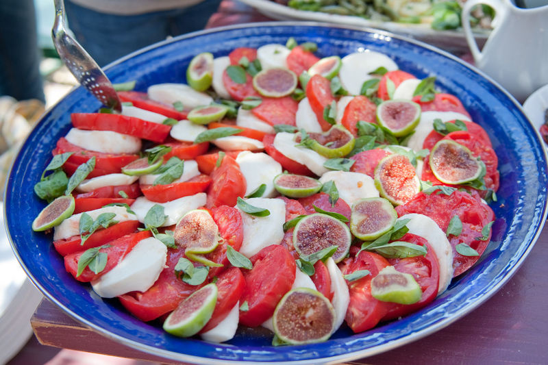 High angle view of fresh caprese salad with fig served in plate
