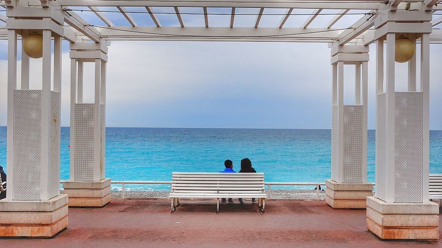 Rear View Of People Sitting On Bench At Pier While Looking At Horizon