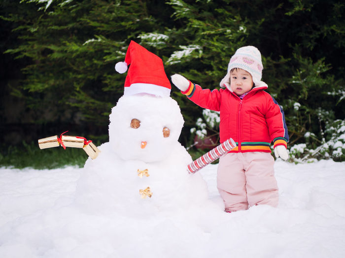 White Christmas Asian Baby Girl Baby Girl Childhood Christmas Decoration Day Full Length Happiness One Person Outdoors People Real People Smiling Snowman Tree Warm Clothing