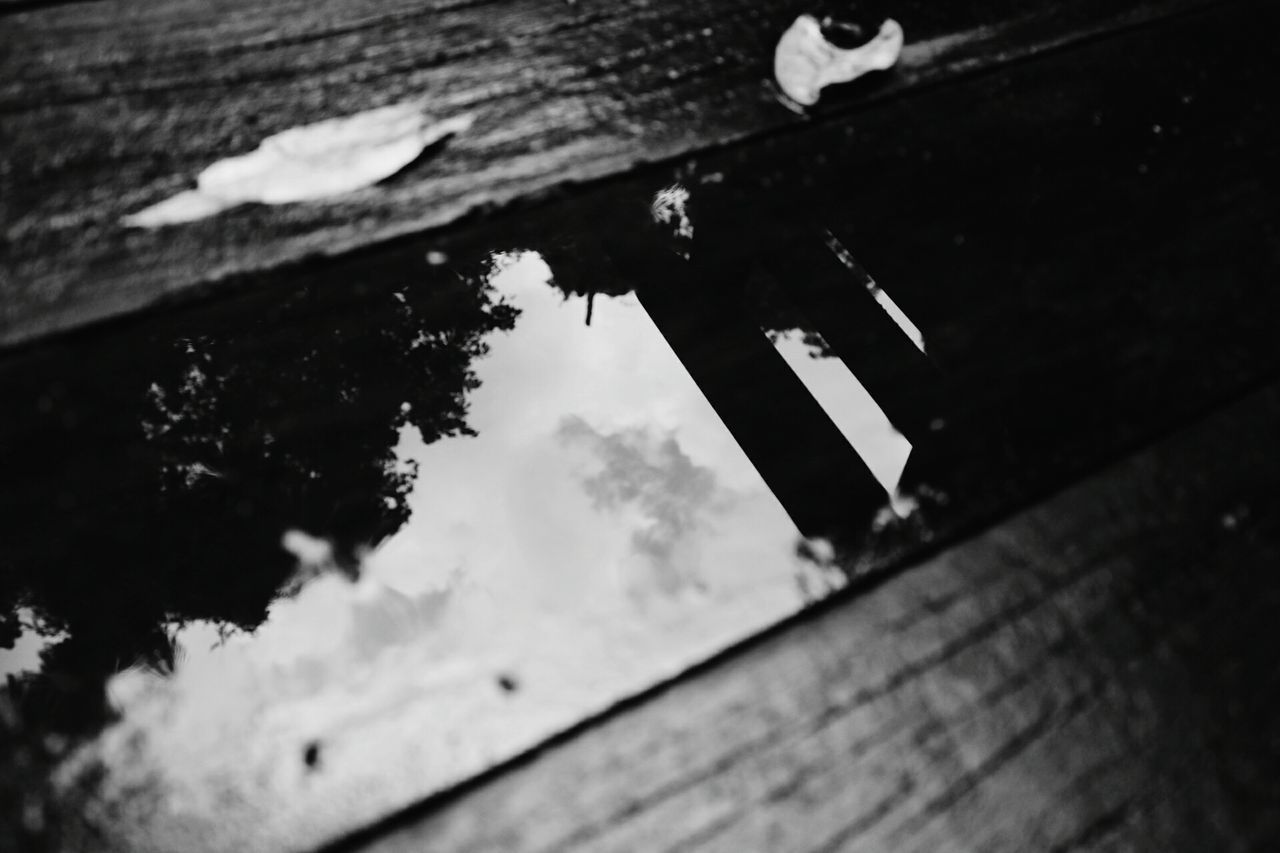 wood - material, day, no people, low angle view, reflection, outdoors, close-up, selective focus, built structure, nature, architecture, wall - building feature, building exterior, water, focus on foreground, metal, sky, damaged