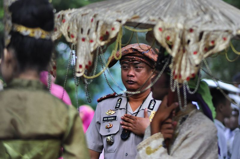 Policeman standing amidst people during traditional ceremony