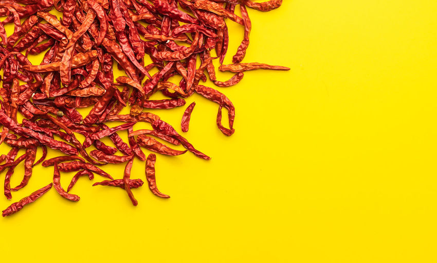 High angle view of red chili on table against yellow background