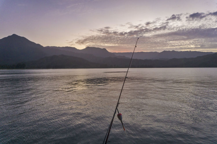 Fishing rod against river and sky at dusk
