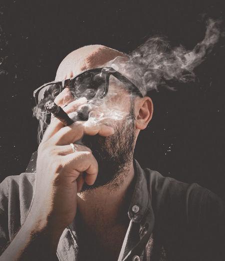 Close-up of man smoking cigar against black background