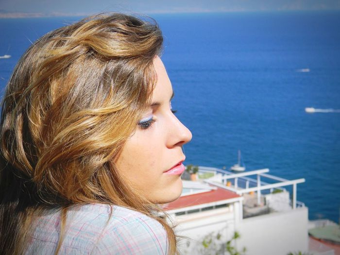 Side view of thoughtful woman against sea