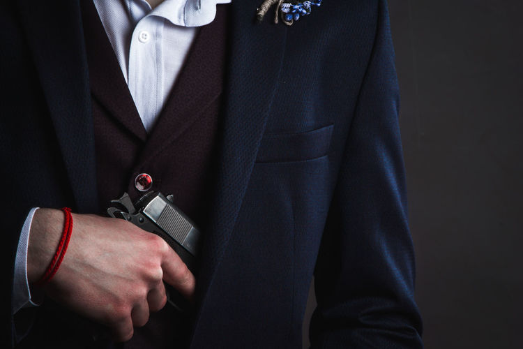 Midsection of man holding handgun against black background