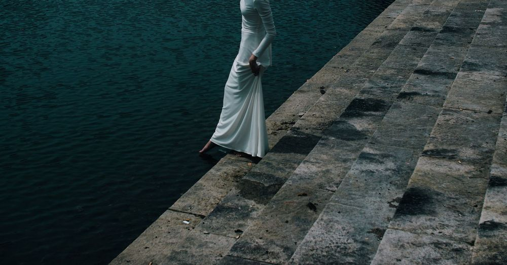 Low section of woman wearing dress walking down steps towards river