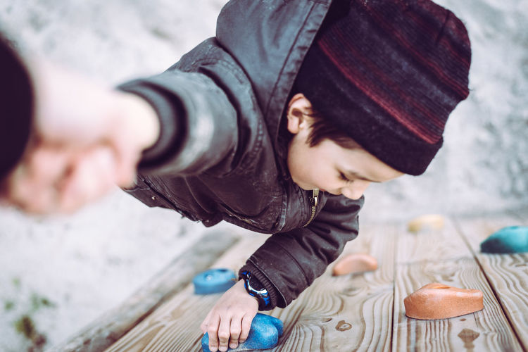 Trust Boy Cheerful Child Childhood Children Only Climbing Cute Day Fun Happiness Holding Hands Human Body Part Human Hand Knit Hat One Person Outdoors People Trust Warm Clothing Young This Is Family
