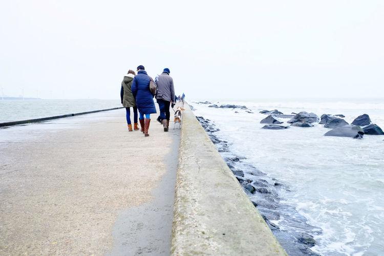 People Walking On Pier In Sea At Hook Of Holland Against Sky