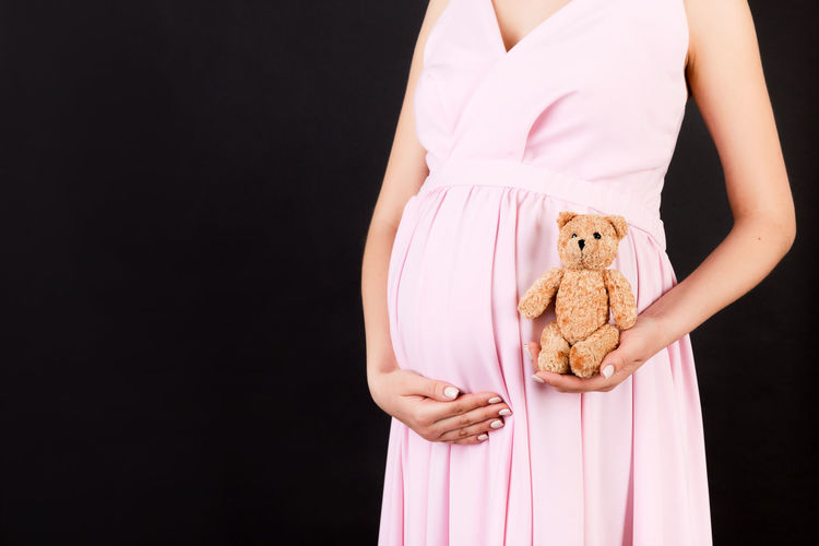 Midsection of woman holding toy while standing against black background