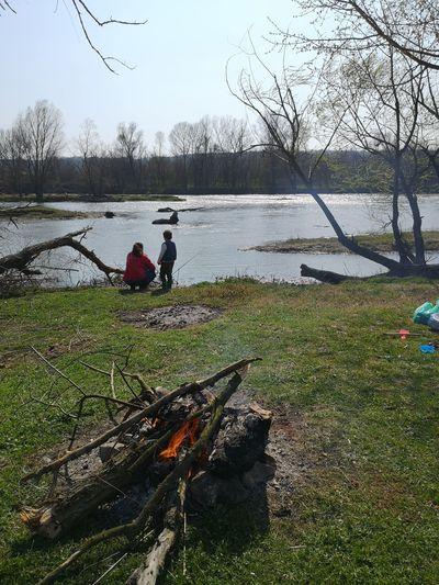 People relaxing on log by lake against sky