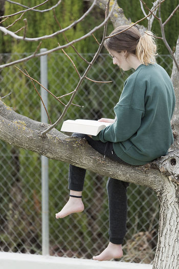 Side view of teenage girl reading book while sitting on tree